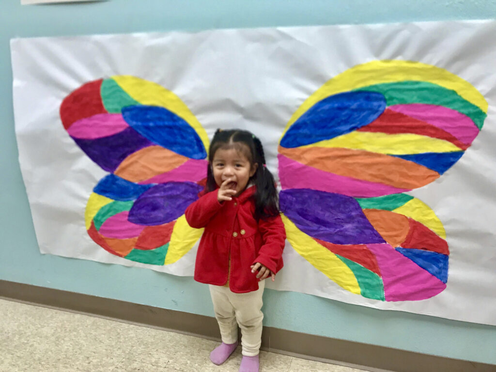 Smiling toddler standing in front of a colorful butterfly mural.